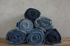 Stack roll blue denim jeans on wood Stock Photography