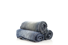 Stack of rolled blue jeans on white background. stock image