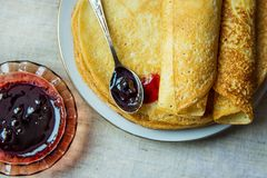 Stack of Rolled Golden Crepes on White Plate Black Currant Jam in Crystal Rosette Spoon Linen Tablecloth royalty free stock images