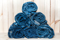 Stack of rolled jeans isolated on wooden background royalty free stock photography