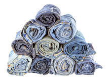 Stack of rolled jeans on white background stock photo
