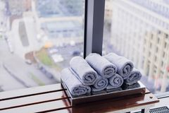 Stack of rolled towels in hotel at gym with city view.  royalty free stock photos