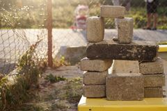 Stack of rough natural brown uneven different sizes and forms stone concrete blocks for foundation on construction site balanced. Like toy house wall and window stock photo