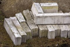 Stack of rough natural brown uneven different sizes and forms stone concrete cement blocks for foundation or wall construction on. Dirty ground background stock photography