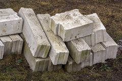 Stack of rough natural brown uneven different sizes and forms stone concrete cement blocks for foundation or wall construction on. Dirty ground background stock image