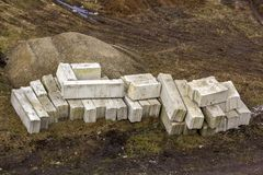 Stack of rough natural brown uneven different sizes and forms stone concrete cement blocks for foundation or wall construction on. Dirty ground background royalty free stock photo