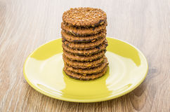 Stack of round brown biscuits in yellow saucer on table Stock Image