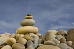 Stack of round peebles with blue sky - zen and spa Royalty Free Stock Image
