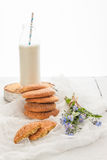 A stack of round shortbread cookies, a bottle of milk and a bouq Royalty Free Stock Photo