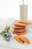 A stack of round shortbread cookies, a bottle of milk and a bouq Stock Photography