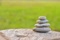 Stack of round smooth stones on a seashore. Stack of round smooth stones on wood Royalty Free Stock Images