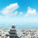 Stack of rounded stones zen-like and blue sky with clouds. Soft focus Stock Photo