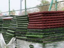 Stack of rubber floor tile mats and artificial turf grass rug tiles for elastic safety flooring. Eco safety surfacing mats are a stock photography