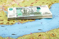 A stack of 1000 ruble Russian bills on the map of Lake Baikal, Siberia, Russia. Tourism, travel, life, environment, investment, expenses concept Stock Photos