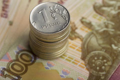 A stack of Russian coins. On background of banknotes Stock Photo