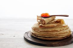 Stack of russian thin pancakes blini with red caviar. Shrovetide Maslenitsa festival meal. On white background. Close up top view with copy space stock images
