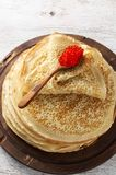 Stack of russian thin pancakes blini with red caviar. Shrovetide Maslenitsa festival. Meal on white wooden background. Rustic style, close up view stock image