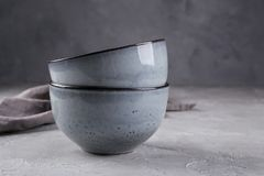Stack of rustic style handcraft bowls in neutral tones against shabby grey wall. Simple tableware stock image