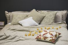 Stack sänglinnar, stack kuddefall, kuddar, överkast, grå beiga färgar, skandinavisk stil royaltyfri foto