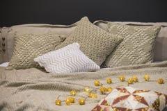 Stack sänglinnar, stack kuddefall, kuddar, överkast, grå beiga färgar, skandinavisk stil arkivfoto