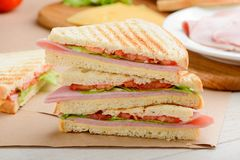 Stack of sandwich triangles. Crunchy crust with beautiful grilled marks and tasty filling of ham, tomato, lettuce and cheese royalty free stock photos