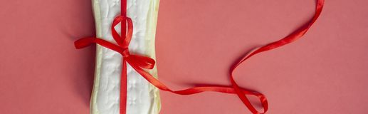 A stack of sanitary pads or Feminine hygiene pads tied with a red ribbon on a pink background. Critical days, Intimate, Period. Days concept stock images
