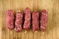Stack of sausages. Five sausages on wooden background Stock Photography