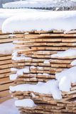 Stack of sawn planks covered with snow Royalty Free Stock Photos