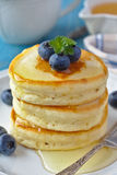 A stack of scotch pancakes with with honey and blueberries on a breakfast table Stock Photography