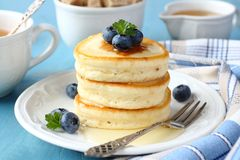 A stack of scotch pancakes with with honey and blueberries on a breakfast table Royalty Free Stock Image