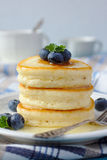 A stack of scotch pancakes with with honey and blueberries on a breakfast table Stock Image