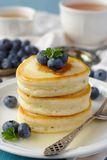 A stack of scotch pancakes with with honey and blueberries on a breakfast table Royalty Free Stock Images