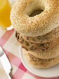 Stack of Seeded Bagels. With a Glass of Orange Juice Stock Photos