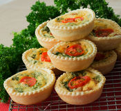 Stack of Small Individual Quiche With Parsley. Small individual quiche each topped with a slice of tomato stacked on a wire cooling rack. A bunch of parsley Royalty Free Stock Photo