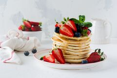 Stack of small pancakes for breakfast with strawberries, blueberries and sweet sauce on a light background. Selective focus