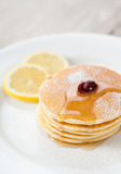 Stack of small pancakes with honey and lemon Royalty Free Stock Photography