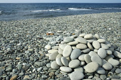 stack of small smooth stones on shore Royalty Free Stock Photo