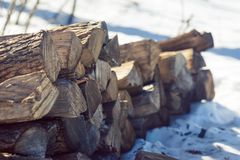 A stack of split firewood on snow covered ground stock image