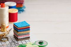 Stack of square pieces of colorful fabrics, accessories for quilting stock image