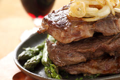 Stack Of Steaks. Fried onions on top of a stack of beef steaks Stock Photography