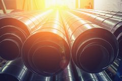 Stack of steel or metal pipes or round tubes as industrial background with perspective. And sunshine effect, toned Stock Photos