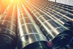 Stack of steel or metal pipes or round tubes as industrial background with perspective and sunshine effect. Toned Royalty Free Stock Photos
