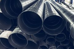 Stack of steel or metal pipes or round tubes as industrial background with perspective. Toned Stock Photo