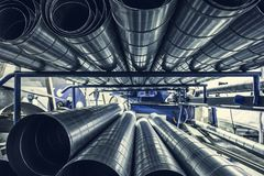 Stack of steel or metal pipes or round tubes as industrial background with perspective. Toned Royalty Free Stock Image