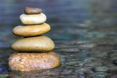 Stack of stones balancing on top in blue water of the river Stock Images
