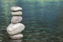 Stack of stones balancing on top in blue water of the river Royalty Free Stock Image