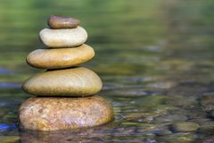 Stack of stones balancing on top in green water of the river.  royalty free stock images