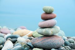 Stack of stones on the beach and sea background Stock Photo