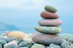 Stack of stones on the beach and sea background Stock Image