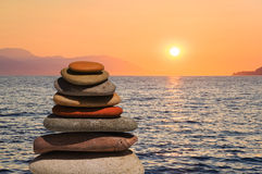 Stack of stones on beach at sunset Stock Photo